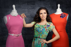 Mujer elegante en tienda de la moda entre maniquíes fotos de archivo