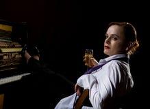 Mujer elegante en una camisa y un lazo blancos que se sientan al lado del piano y del champán de las bebidas imágenes de archivo libres de regalías