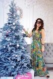 Mujer elegante en una máscara negra del carnaval que coloca la Navidad cercana t Fotografía de archivo