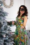 Mujer elegante en una situación negra de la máscara del carnaval cerca del árbol de navidad y del champán el sostenerse en su ves foto de archivo