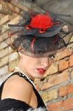 Mujer elegante en vestido y sombrero negros con velo Fotos de archivo libres de regalías