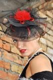 Mujer elegante en vestido y sombrero negros con velo Imagen de archivo libre de regalías
