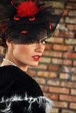 Mujer elegante en vestido y sombrero negros con velo Foto de archivo