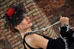 Mujer elegante en vestido y sombrero negros con velo Fotografía de archivo
