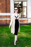 Mujer elegante europea rubia de la moda feliz con los labios rojos y la piel blanca que se colocan en el edificio de ladrillo roj Imagen de archivo libre de regalías