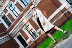 Mujer elegante europea rubia de la moda feliz con los labios rojos y la piel blanca que se colocan en el edificio de ladrillo roj Imagen de archivo