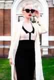 Mujer elegante europea rubia de la moda feliz con los labios rojos y la piel blanca que se colocan en el edificio de ladrillo roj Foto de archivo