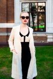 Mujer elegante europea rubia de la moda feliz con los labios rojos y la piel blanca que se colocan en el edificio de ladrillo roj Foto de archivo libre de regalías