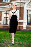 Mujer elegante europea rubia de la moda feliz con los labios rojos y la piel blanca que se colocan en el edificio de ladrillo roj Imagenes de archivo