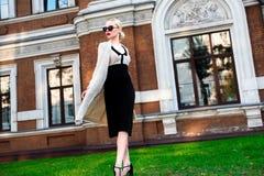 Mujer elegante europea rubia de la moda feliz con los labios rojos y la piel blanca que se colocan en el edificio de ladrillo roj Fotos de archivo libres de regalías