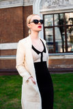 Mujer elegante europea rubia de la moda feliz con los labios rojos y la piel blanca que se colocan en el edificio de ladrillo roj Fotografía de archivo