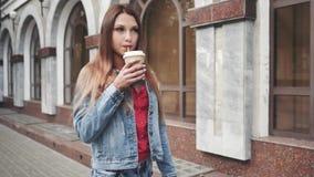 Mujer elegante feliz joven que camina en el centro de ciudad y el café de consumición almacen de video