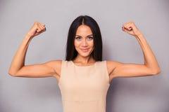 Mujer elegante feliz que muestra su bíceps Foto de archivo