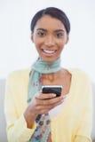 Mujer elegante feliz que se sienta en envío de mensajes de texto del sofá Foto de archivo