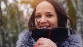 Mujer elegante hermosa de las sonrisas que se coloca en un parque en otoño Fotos de archivo libres de regalías