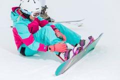 Mujer elegante hermosa joven que ata con correa en su snowboard imágenes de archivo libres de regalías
