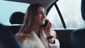 Mujer elegante hermosa que discute tareas importantes con su socio, que la llamó mientras que ella conducía al trabajo almacen de metraje de vídeo