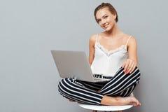 Mujer elegante hermosa sonriente que usa el ordenador de la PC del ordenador portátil para el estudio Fotografía de archivo