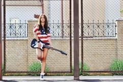 Mujer elegante joven con el retrato al aire libre de la moda de la guitarra Imagenes de archivo