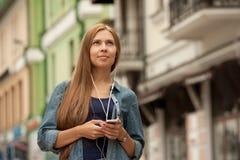 Mujer elegante joven con los auriculares y el teléfono Fotografía de archivo