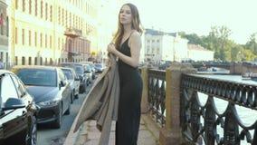 Mujer elegante joven del inconformista que camina en calle en el puente, sacando una capa metrajes