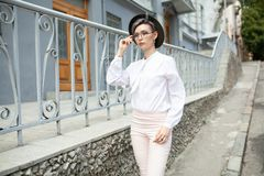 Mujer elegante joven del inconformista que lleva los vidrios y el sombrero que se colocan cerca de la cerca en la ciudad imagenes de archivo