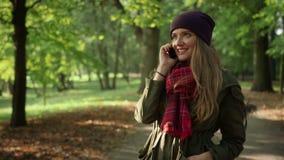 Mujer elegante joven que habla en el teléfono celular en el parque del otoño metrajes