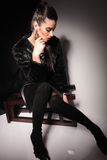 Mujer elegante joven que se sienta en un taburete Fotos de archivo libres de regalías