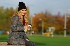 Mujer elegante joven que sonríe con café en un parque foto de archivo