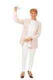 Mujer elegante mayor de la sonrisa que lleva a cabo un avión del juguete Fotos de archivo libres de regalías