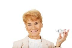 Mujer elegante mayor de la sonrisa que lleva a cabo un avión del juguete Imágenes de archivo libres de regalías