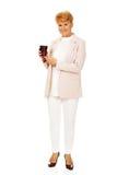 Mujer elegante mayor de la sonrisa que sostiene la taza de papel Imagen de archivo