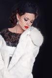 Mujer elegante que desgasta en el abrigo de pieles blanco aislado en backgr negro Fotos de archivo libres de regalías