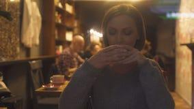 Mujer elegante que disfruta del aroma y del gusto del café caliente que se sientan en café después de trabajo almacen de metraje de vídeo