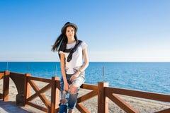 Mujer elegante que disfruta del buenos tiempo y vacaciones soleados mientras que se sienta en la playa Fotografía de archivo libre de regalías