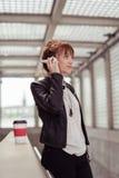 Mujer elegante que escucha la música en las verjas Fotografía de archivo libre de regalías
