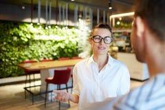 Mujer elegante que habla con el hombre en cafetería imágenes de archivo libres de regalías