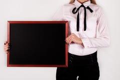 Mujer elegante que lleva a cabo la pizarra vacía en manos y el espacio para el texto a bordo fotos de archivo