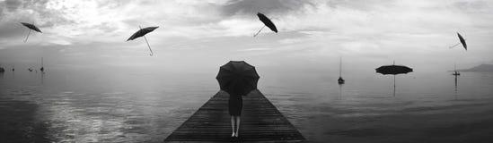 Mujer elegante que repara de la lluvia de los paraguas de los negros Foto de archivo libre de regalías