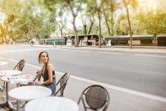Mujer elegante que se sienta en el café francés Imagen de archivo libre de regalías