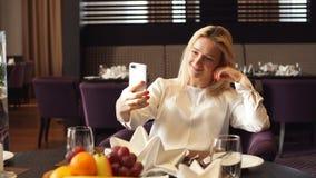 Mujer elegante que se sienta en el café y que toma el selfie con su teléfono elegante almacen de metraje de vídeo