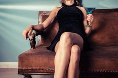 Mujer elegante que se sienta en el sofá con el cóctel Fotos de archivo