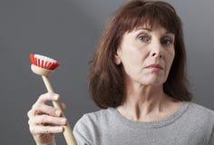 Mujer elegante 50s que entrega el cepillo del plato para lavarse y limpiar en casa foto de archivo