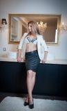 Mujer elegante sensual en el equipo de la oficina que permanece delante de un espejo grande. Mujer joven rubia hermosa y atractiva Fotografía de archivo libre de regalías