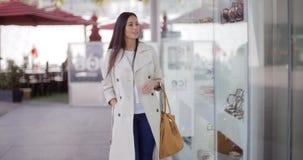 Mujer elegante sonriente que camina más allá de una tienda metrajes