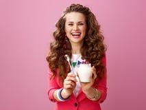 Mujer elegante sonriente que muestra a granja el yogur y la cuchara orgánicos imagenes de archivo