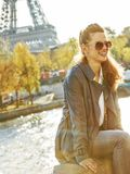 Mujer elegante sonriente que se sienta en el parapeto en París, Francia fotografía de archivo libre de regalías