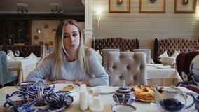 Mujer elegante té que come, de la consumición y hablando en el restaurante de moda metrajes