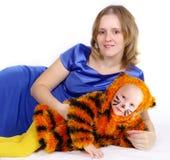 Mujer elegante y la muchacha en un juego de un tigre Fotos de archivo