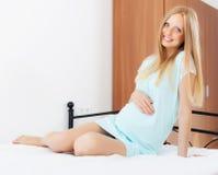 Mujer embarazada alegre que se sienta en la hoja blanca Fotos de archivo libres de regalías